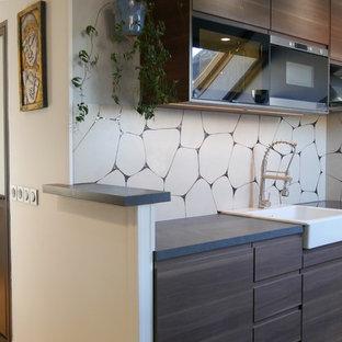 Exemple d'une cuisine linéaire tendance avec un évier de ferme, un placard à porte plane, des portes de placard en bois sombre, une crédence jaune, un électroménager noir, un sol gris et un plan de travail gris.