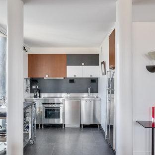 パリの中サイズのエクレクティックスタイルのおしゃれなキッチン (シングルシンク、アイランドなし、黒い床、インセット扉のキャビネット、茶色いキャビネット、ステンレスカウンター、グレーのキッチンパネル、スレートの床、シルバーの調理設備の、セラミックタイルの床) の写真