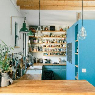 Cette photo montre une cuisine industrielle en U avec un évier encastré, un placard à porte plane, des portes de placard turquoises, un plan de travail en bois, une crédence blanche, une péninsule et un plan de travail marron.
