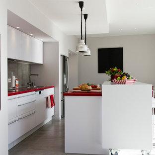 Ejemplo de cocina lineal, contemporánea, de tamaño medio, abierta, con fregadero bajoencimera, armarios con rebordes decorativos, puertas de armario blancas, encimera de laminado, salpicadero verde, electrodomésticos de acero inoxidable, una isla y encimeras rojas