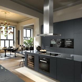 Idées déco pour une très grand cuisine ouverte parallèle contemporaine avec un placard à porte plane, des portes de placard noires, un électroménager noir, un îlot central, un sol marron et un plan de travail noir.