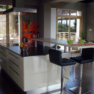 Esempio di una grande cucina minimalista con lavello a doppia vasca, ante lisce, ante beige, top in laminato, paraspruzzi arancione, paraspruzzi con lastra di vetro, elettrodomestici in acciaio inossidabile, pavimento in compensato, isola e pavimento marrone
