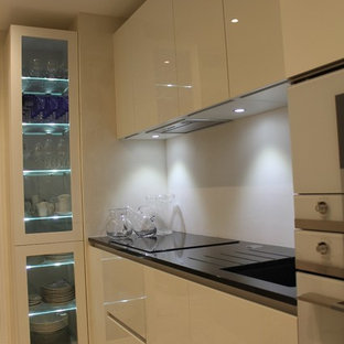 Design ideas for a small modern single-wall enclosed kitchen in Nice with an integrated sink, flat-panel cabinets, granite worktops, white splashback, mirror splashback, white appliances, marble flooring, no island, beige floors and black worktops.