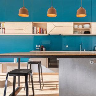 Aménagement d'une cuisine ouverte parallèle contemporaine de taille moyenne avec un évier 1 bac, un placard à porte affleurante, des portes de placard en bois clair, un plan de travail en béton, une crédence en feuille de verre, un électroménager encastrable, un sol en bois clair, un îlot central, une crédence bleue et un plan de travail gris.