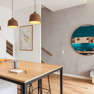 Design ideas for a mid-sized contemporary galley open plan kitchen in Paris with a single-bowl sink, beaded inset cabinets, light wood cabinets, concrete benchtops, glass sheet splashback, panelled appliances, light hardwood floors, with island, blue splashback and grey benchtop.