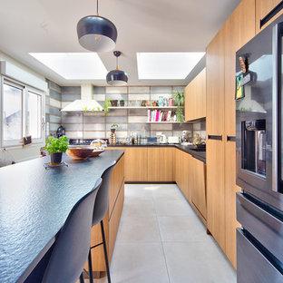Idées déco pour une cuisine classique en L fermée avec un placard à porte plane, des portes de placard en bois brun, une crédence grise, un électroménager en acier inoxydable, un îlot central, un sol beige et un plan de travail noir.