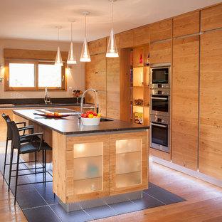 Cette image montre une grande cuisine américaine chalet en L avec un placard à porte plane, des portes de placard en bois brun, un électroménager en acier inoxydable, un sol en bois brun et un îlot central.