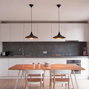 Idées déco pour une cuisine américaine linéaire moderne de taille moyenne avec une crédence grise, aucun îlot, des portes de placard grises, un placard à porte affleurante, un sol en bois clair et un plan de travail gris.