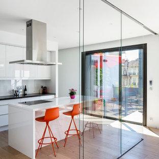 Exemple d'une cuisine américaine parallèle tendance de taille moyenne avec un placard à porte plane, des portes de placard blanches, un plan de travail en stratifié, une crédence blanche, un électroménager noir, un sol en bois brun et un îlot central.