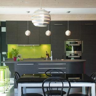 Idée de décoration pour une cuisine américaine parallèle design de taille moyenne avec un placard à porte plane, des portes de placard grises, une crédence verte, une crédence en feuille de verre, un électroménager en acier inoxydable et un îlot central.