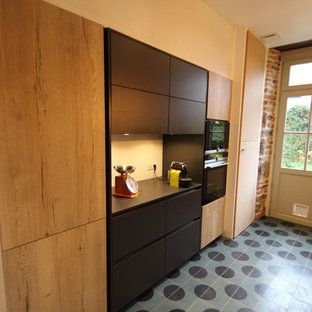 This is an example of a mid-sized industrial galley separate kitchen in Rennes with an integrated sink, flat-panel cabinets, black cabinets, granite benchtops, black splashback, black appliances, cement tiles, turquoise floor and black benchtop.