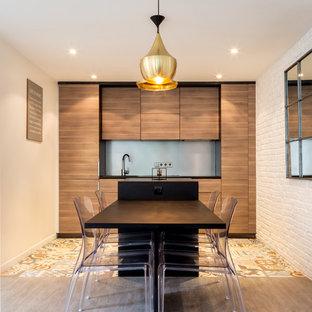 Cette image montre une grand cuisine ouverte linéaire design avec des portes de placard en bois brun, un évier encastré, un placard à porte affleurante, un plan de travail en bois, une crédence grise, un sol en carreaux de ciment, un îlot central et un plan de travail noir.