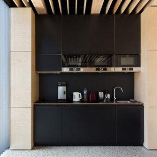 На фото: маленькая прямая кухня в современном стиле с накладной раковиной, плоскими фасадами, черными фасадами, черным фартуком, техникой под мебельный фасад, полом из терраццо, серым полом и черной столешницей без острова