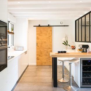 Inspiration pour une grande cuisine nordique avec des portes de placard blanches, un plan de travail en quartz, un sol en carrelage de céramique, un sol gris, un plan de travail blanc, un placard à porte plane, un électroménager noir et une péninsule.