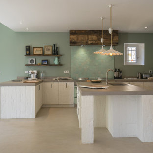 This is an example of a mid-sized country u-shaped eat-in kitchen in Other with an undermount sink, beaded inset cabinets, white cabinets, concrete benchtops, green splashback, ceramic splashback, coloured appliances, concrete floors, multiple islands, grey floor and grey benchtop.