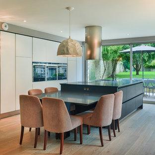 Inspiration pour une cuisine américaine parallèle design de taille moyenne avec un sol en bois brun, un placard à porte plane, des portes de placard blanches et un îlot central.