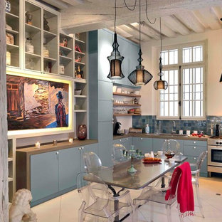 Inspiration for a large transitional kitchen pantry in Nice with an undermount sink, blue cabinets, wood benchtops, blue splashback, matchstick tile splashback, stainless steel appliances, ceramic floors, with island, beige floor and brown benchtop.