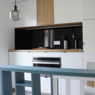 This is an example of a small contemporary galley open plan kitchen in Paris with a single-bowl sink, beaded inset cabinets, white cabinets, wood benchtops, black splashback, glass tile splashback, stainless steel appliances, laminate floors, with island, brown floor and brown benchtop.