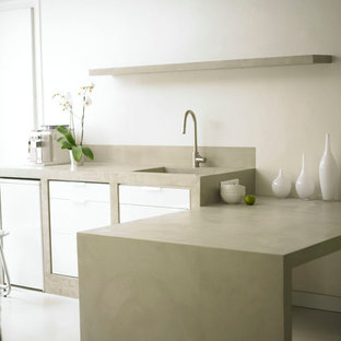 Esempio di una cucina moderna di medie dimensioni con ante bianche, top in cemento e penisola