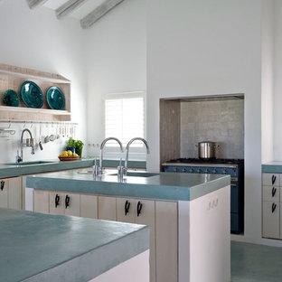 Réalisation d'une grand cuisine champêtre en U fermée avec des portes de placard en bois clair et 2 îlots.
