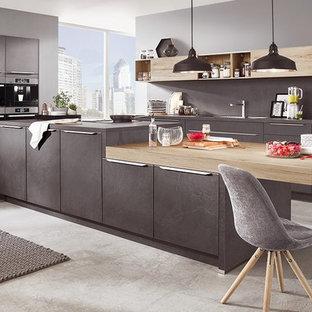 Aménagement d'une très grande cuisine ouverte contemporaine en U avec des portes de placard grises, une crédence grise, un électroménager en acier inoxydable, béton au sol, un îlot central et un sol gris.