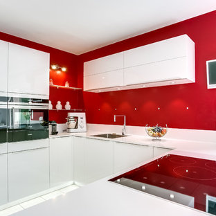 Contemporary eat-in kitchen remodeling - Example of a trendy u-shaped eat-in kitchen design in Paris with an undermount sink, flat-panel cabinets, white cabinets, red backsplash and white appliances