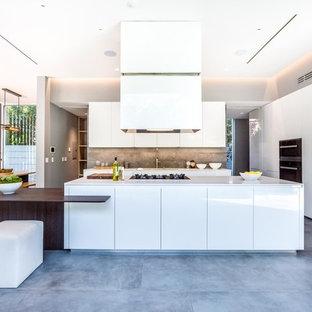 Exemple d'une cuisine américaine tendance avec un plan de travail en quartz, une crédence grise, une crédence en carrelage de pierre, un électroménager noir, un sol en carrelage de céramique, un îlot central, un sol gris, un placard à porte plane et des portes de placard blanches.
