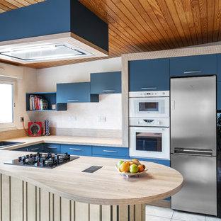 Idées déco pour une cuisine contemporaine en U avec un évier posé, un placard à porte plane, des portes de placard bleues, un plan de travail en bois, une péninsule, un sol gris et un plan de travail beige.