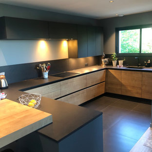 This is an example of a mid-sized industrial u-shaped eat-in kitchen in Lyon with an undermount sink, light wood cabinets, solid surface benchtops, black splashback, slate splashback, stainless steel appliances, light hardwood floors, no island and black benchtop.