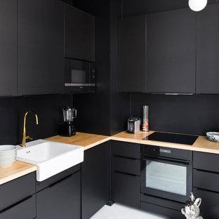 パリの中くらいのトラディショナルスタイルのおしゃれなキッチン (エプロンフロントシンク、フラットパネル扉のキャビネット、黒いキャビネット、木材カウンター、黒いキッチンパネル、パネルと同色の調理設備、無垢フローリング、アイランドなし、白い床) の写真