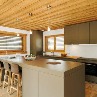 Réalisation d'une cuisine linéaire design avec un îlot central, un placard à porte plane, des portes de placards vertess, un sol en bois brun et un sol marron.