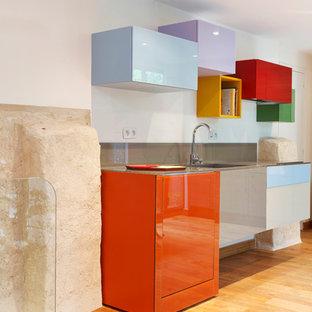 Cette photo montre une cuisine ouverte linéaire tendance de taille moyenne avec un placard à porte plane, une crédence grise, un sol en bois brun et aucun îlot.