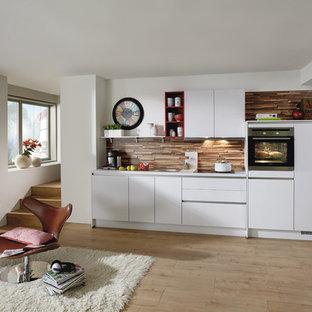 Inspiration pour une cuisine ouverte linéaire nordique de taille moyenne avec des portes de placard blanches, aucun îlot et une crédence marron.