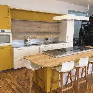 Aménagement d'une cuisine américaine parallèle contemporaine de taille moyenne avec un évier encastré, un placard à porte shaker, des portes de placard blanches, une crédence marron, une crédence en bois, un électroménager de couleur, un sol en bois clair et un îlot central.