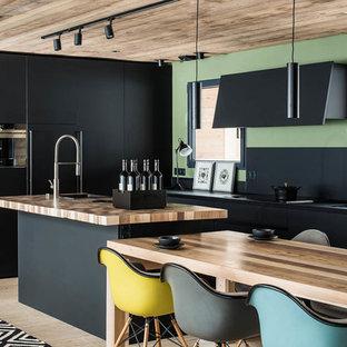 Idées déco pour une cuisine américaine parallèle contemporaine de taille moyenne avec un évier posé, un placard à porte plane, des portes de placard beiges, un plan de travail en bois, une crédence noire, un électroménager noir, un sol en bois clair, un îlot central, un sol beige et un plan de travail marron.