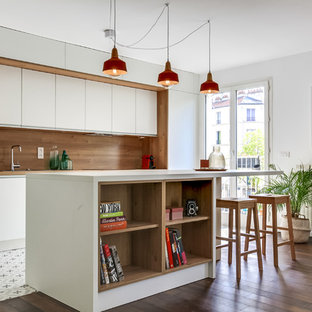 Design ideas for a large midcentury single-wall open plan kitchen in Paris with white cabinets, laminate benchtops, panelled appliances, cement tiles, with island, flat-panel cabinets, brown splashback, timber splashback and multi-coloured floor.