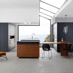 Exemple d'une très grand cuisine américaine tendance en L avec un placard à porte shaker, des portes de placard noires, béton au sol et un îlot central.
