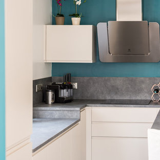 Design ideas for a mid-sized contemporary u-shaped open plan kitchen in Nice with an integrated sink, flat-panel cabinets, white cabinets, laminate benchtops, grey splashback, slate splashback, stainless steel appliances, concrete floors, no island and grey floor.