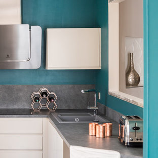 Inspiration for a mid-sized contemporary u-shaped open plan kitchen in Nice with an integrated sink, flat-panel cabinets, white cabinets, laminate benchtops, grey splashback, slate splashback, stainless steel appliances, concrete floors, no island and grey floor.