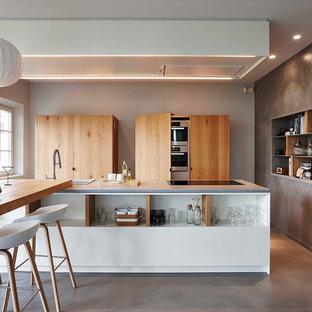 Aménagement d'une cuisine américaine parallèle contemporaine de taille moyenne avec un évier posé, un placard sans porte, des portes de placard en bois brun, un plan de travail en béton, béton au sol et un îlot central.
