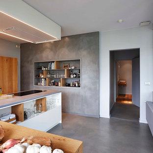 Idées déco pour une cuisine américaine contemporaine en L de taille moyenne avec un placard sans porte, des portes de placard en bois brun, béton au sol, 2 îlots et un plan de travail en bois.