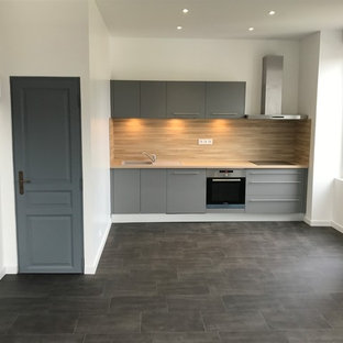 This is an example of a small contemporary single-wall open plan kitchen in Grenoble with an integrated sink, flat-panel cabinets, grey cabinets, laminate benchtops, beige splashback, stainless steel appliances, linoleum floors, no island, grey floor and beige benchtop.