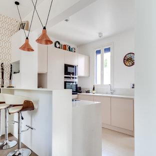Aménagement d'une petite cuisine américaine contemporaine en U avec un placard à porte plane, des portes de placard beiges, un électroménager noir, une péninsule, un évier encastré et une crédence grise.