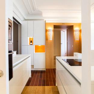 Idées déco pour une cuisine américaine parallèle contemporaine avec un placard à porte plane, des portes de placard blanches, un plan de travail en inox, un électroménager de couleur, un sol en bois clair et un îlot central.