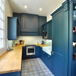 Inspiration for a small transitional u-shaped separate kitchen in Paris with an integrated sink, shaker cabinets, blue cabinets, wood benchtops, white splashback, ceramic splashback, stainless steel appliances and cement tiles.
