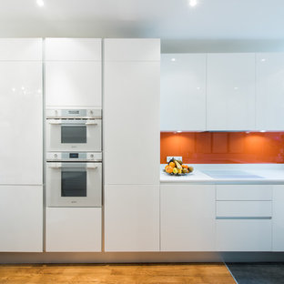 Design ideas for a mid-sized modern u-shaped open plan kitchen in Paris with an integrated sink, beaded inset cabinets, white cabinets, quartzite benchtops, orange splashback, glass tile splashback and panelled appliances.
