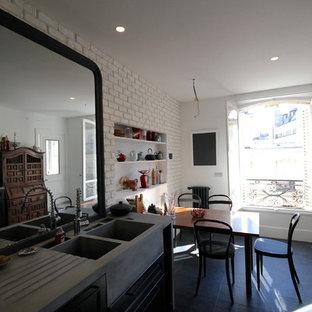 Eklektisk inredning av ett avskilt, stort grå grått u-kök, med en dubbel diskho, luckor med profilerade fronter, svarta skåp, bänkskiva i betong, svart stänkskydd, stänkskydd i skiffer, svarta vitvaror, skiffergolv, flera köksöar och svart golv