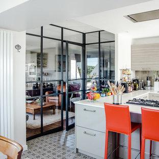 Cette image montre une petit cuisine urbaine en U fermée avec un placard à porte shaker, des portes de placard blanches, un plan de travail en inox, une crédence beige, un sol en carreaux de ciment et aucun îlot.