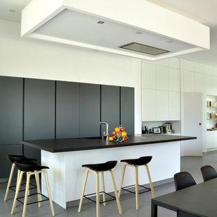 Cette photo montre une cuisine ouverte parallèle tendance de taille moyenne avec un évier intégré, des portes de placard noires, un électroménager encastrable et un îlot central.