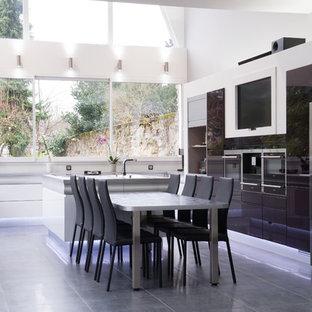 Aménagement d'une grand cuisine ouverte contemporaine en U avec une crédence blanche, un électroménager en acier inoxydable, un îlot central et des portes de placard noires.